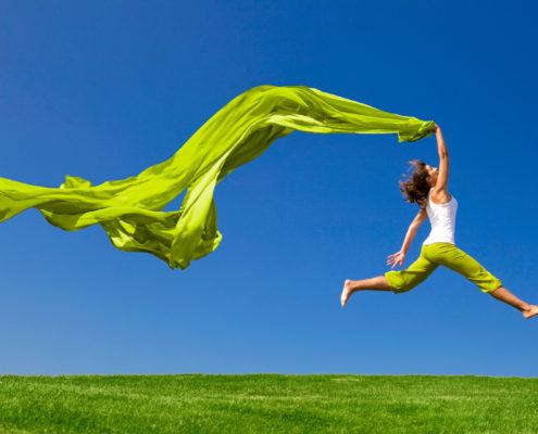 Frau springt im Sommer über eine Wiese mit wehendem Tuch in der Hand