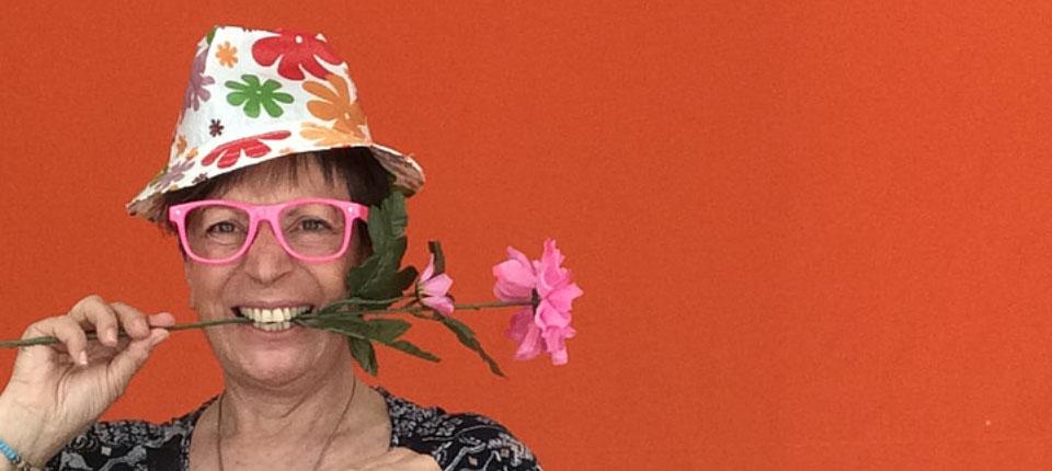 Margit Heuser mit einem witzigen Hut, einer großen Pinken Hornbrille und einer Blume zwischen den Zähnen.