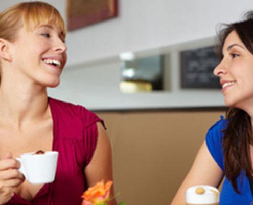 Zwei lachende Frauen mit Kaffee im Café